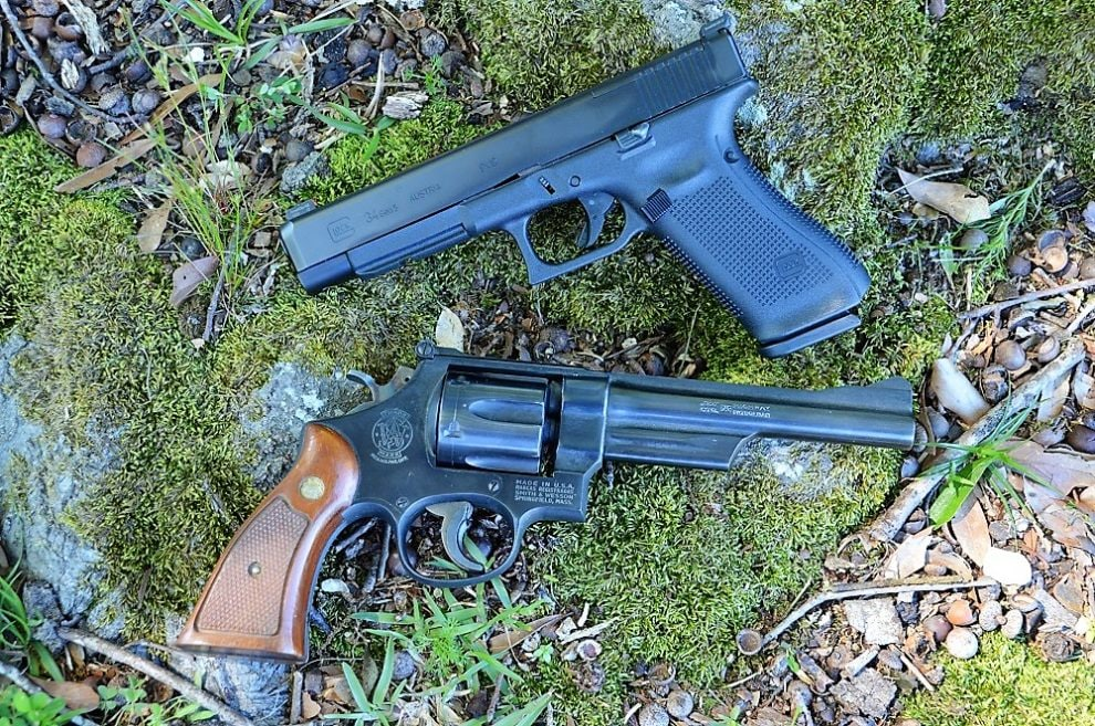 Glock 34 Smith Wesson Model 28 on a mossy tree trunk