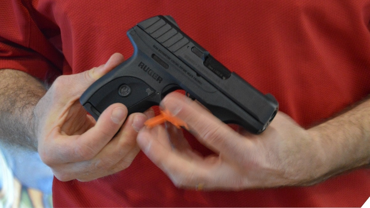 A man in a red shirt holds a Ruger 9mm pistol