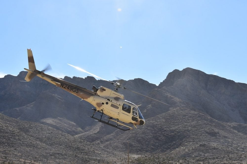 An Airbus A-Star A350 helicopter crossing a mountain