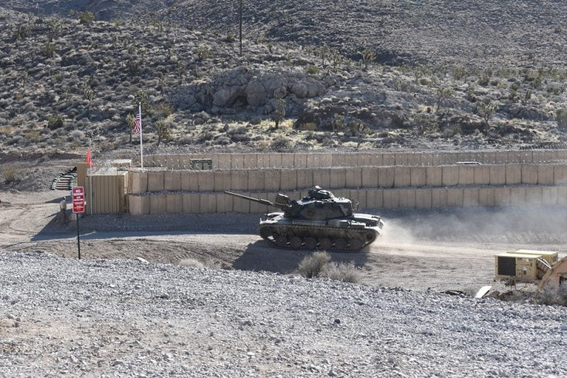 M60 battle tank driving around a tan Hesco barrier compound
