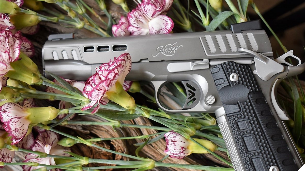kimber rapide M1911 on a wooden block with flowers