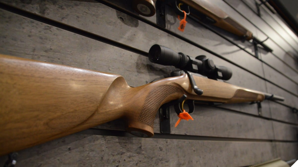 A steyr bolt action rifle rests on the wall