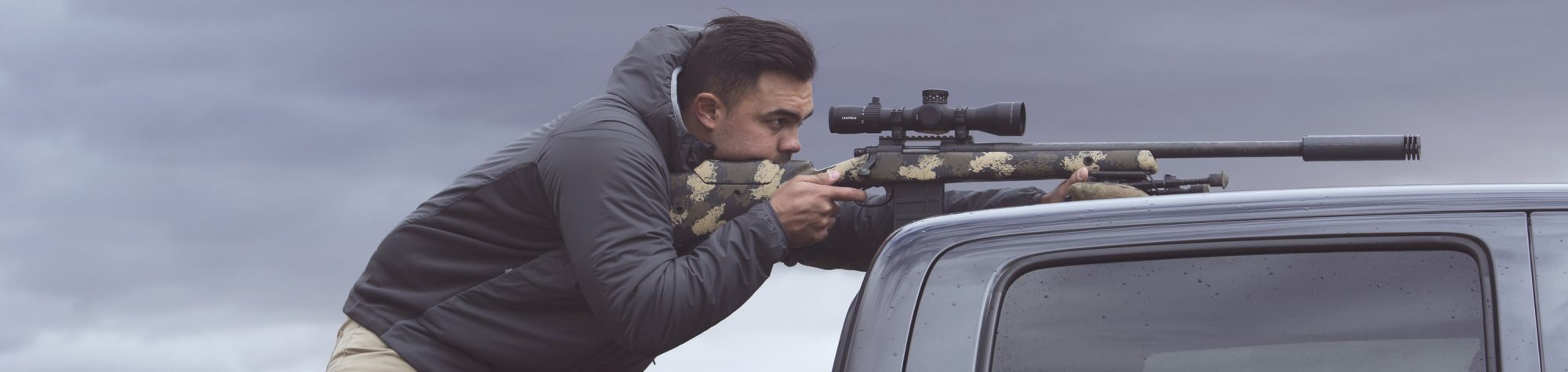 A man aims a rifle through a Leupold Mark 5HD scope on a bolt-action rifle