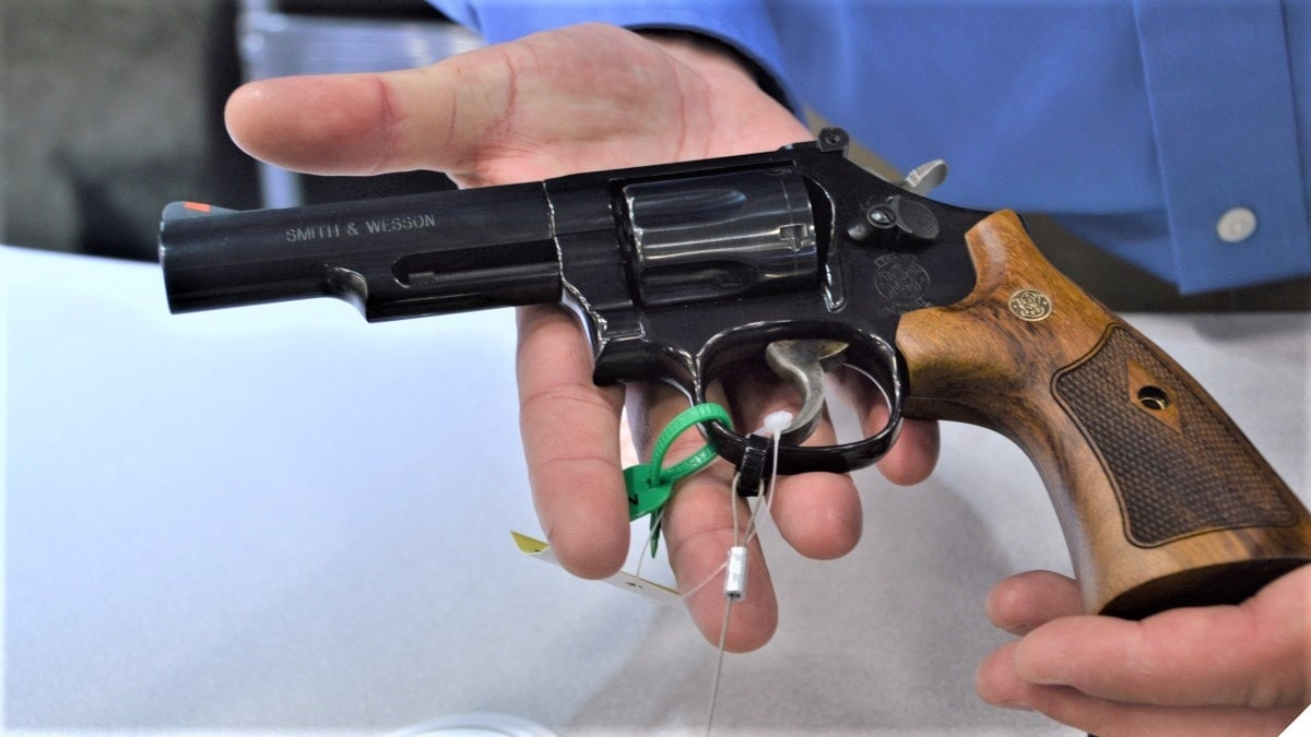 A man holds a beautifully blued S&W K-frame Model 19 .357 Magnum revolver with wood grips