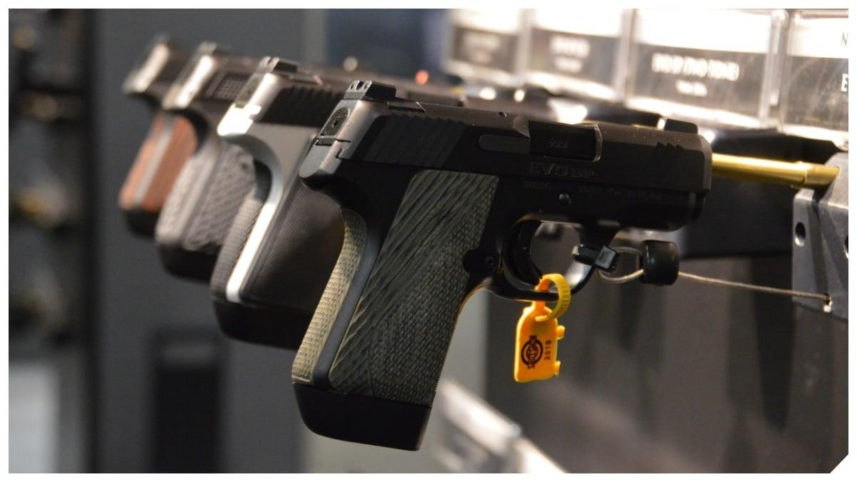 A variety of Kimber semi-auto handguns on a trade show rack.