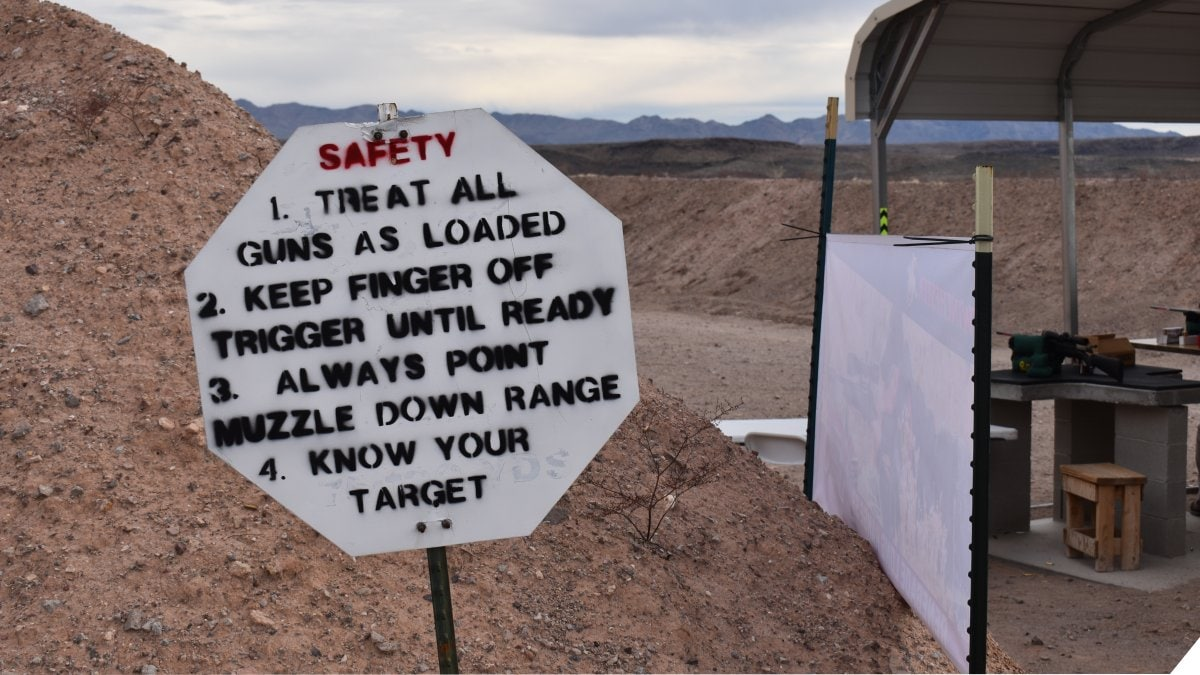 A sign with firearms safety rules written on it at a shooting range