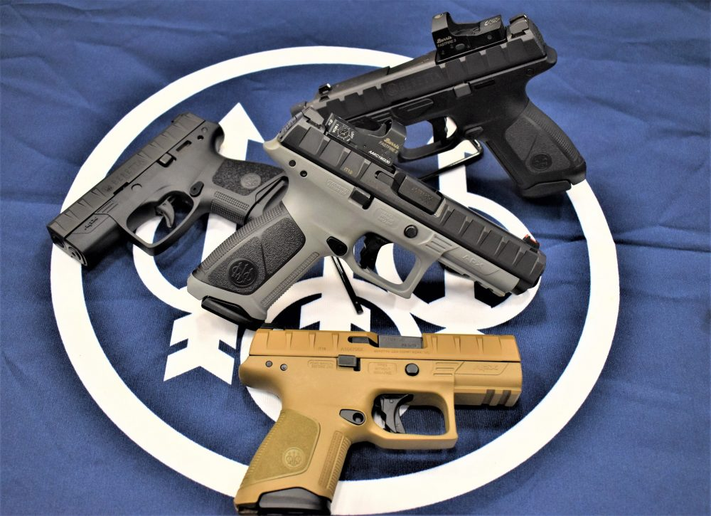 A table top of several Beretta APX pistols in a variety of shapes, sizes and colors