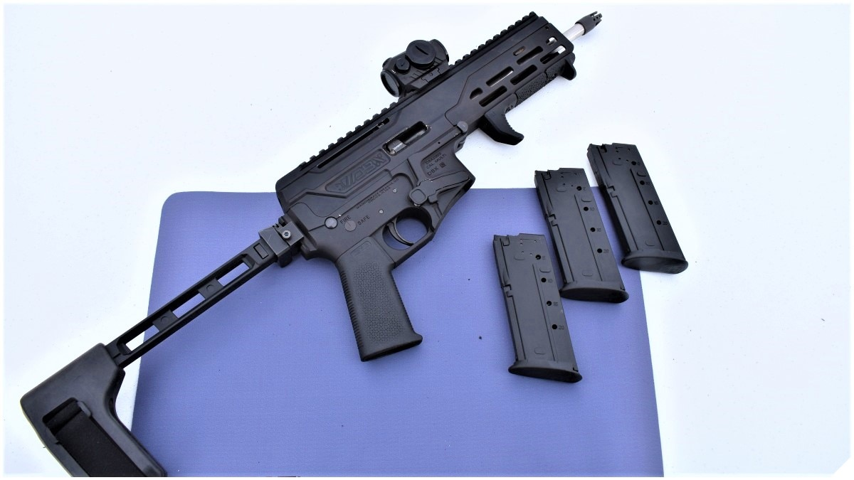 A table with a blue mat on top and a svelte Diamondback DBX 5.87x28mm pistol with folding brace and three FN Five-SeveN magazines next to it.
