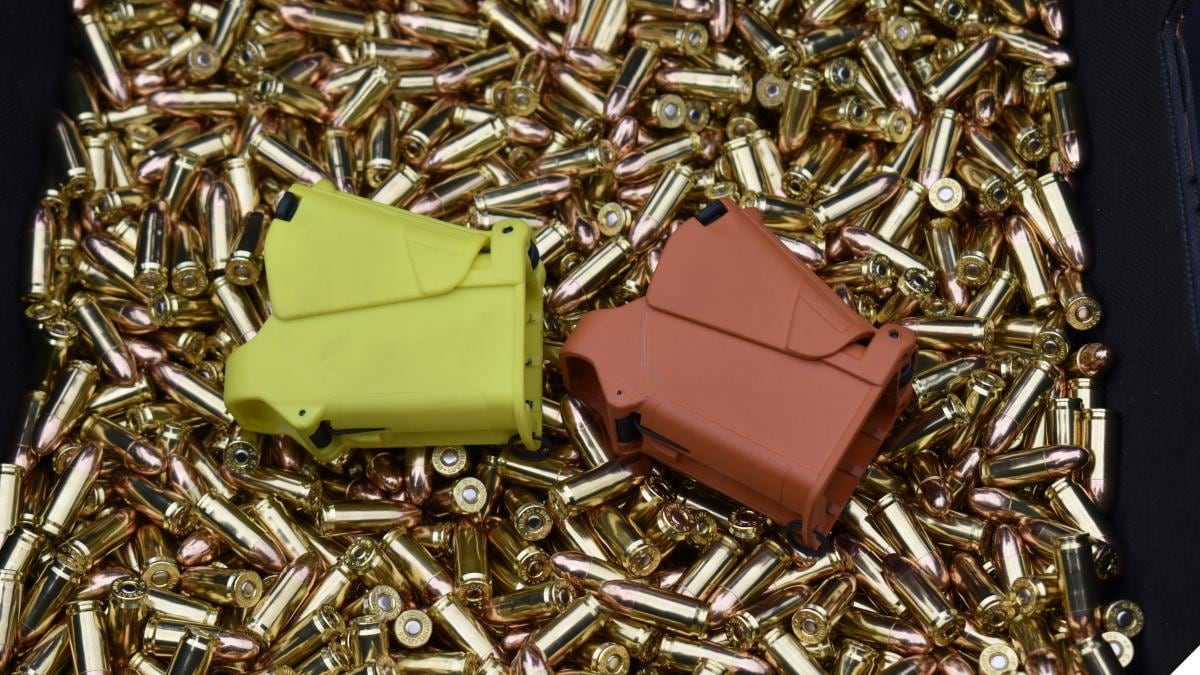 A box of loose 9mm bullets with two magazine loaders on top