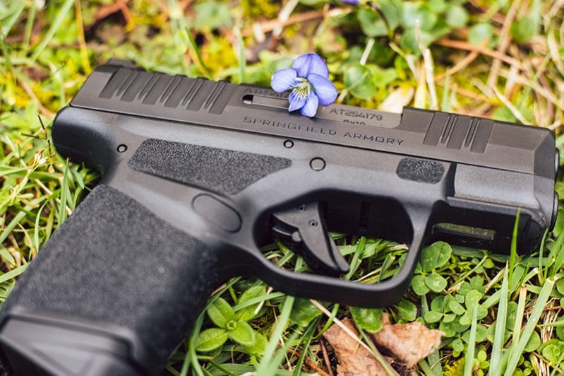 A Springfield Armory Hellcat pistol in a green field of clover with white briar flowers