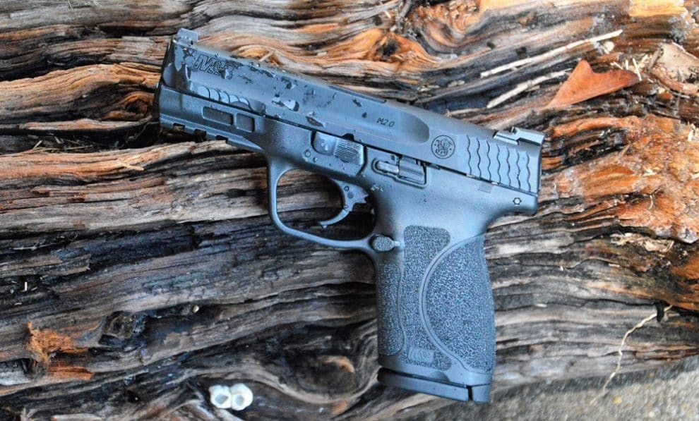 A Smith & Wesson M&P M2.0 Compact on a timber block, freckled with water