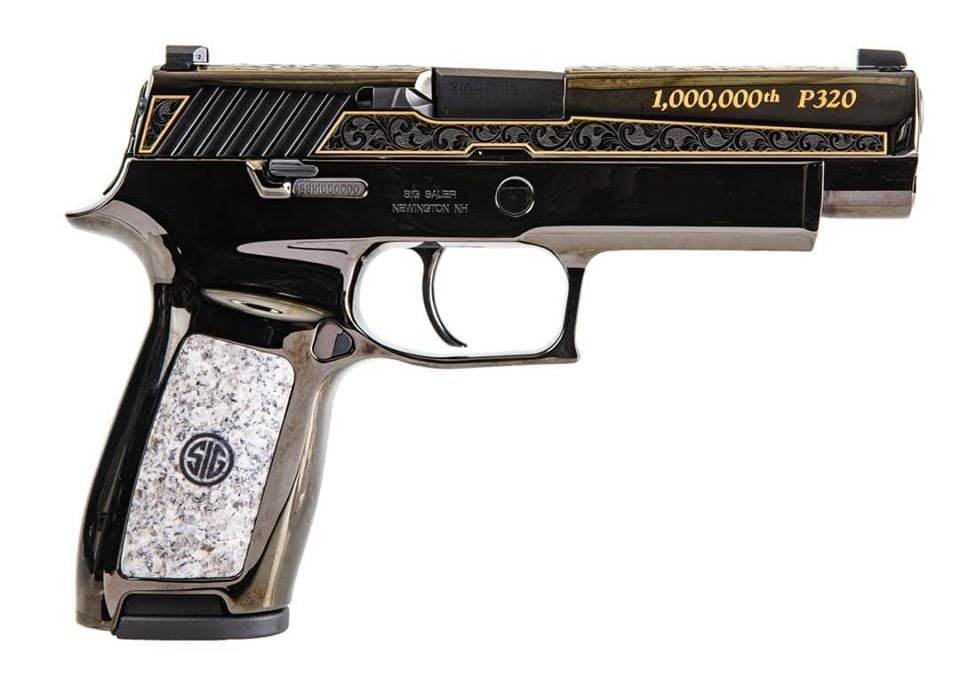 """A close up lightbox shot of an engraved Sig Sauer P320 pistol marked """"1,000,000th"""""""