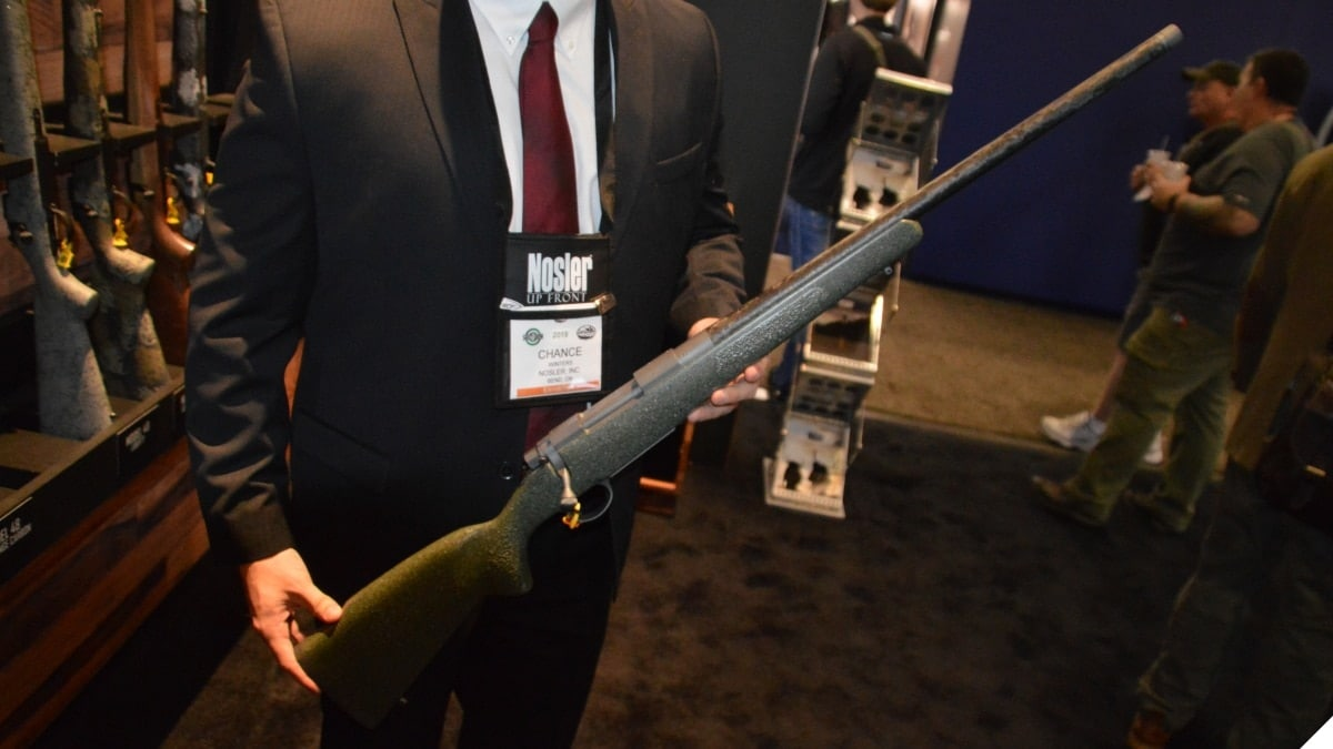 A man in a suit holds a bolt-action Nosler rifle