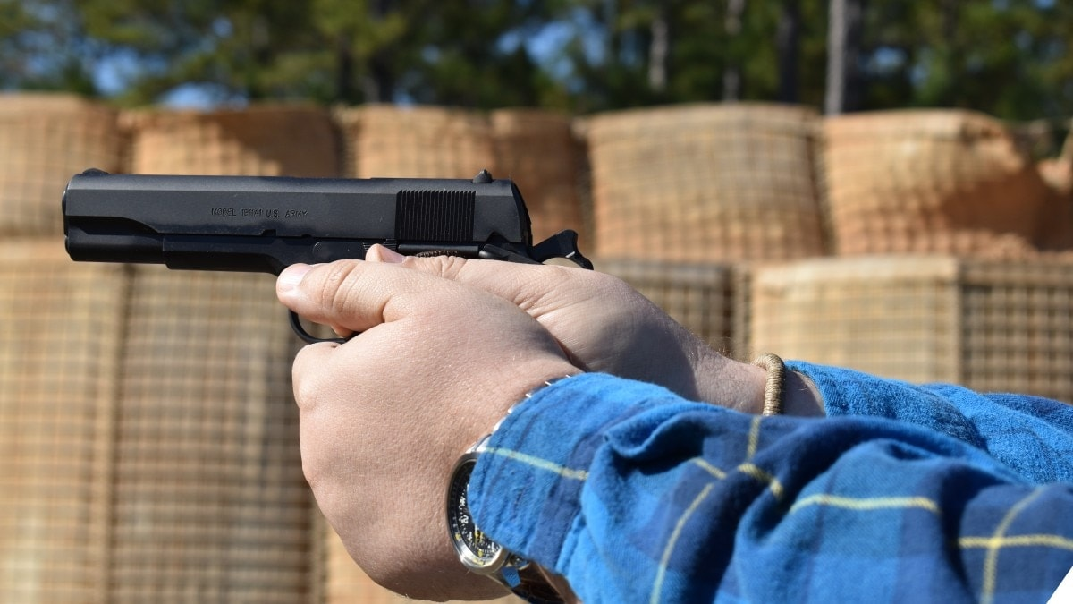 A man in a flannel shirt holding a M1911 pistol at a shooting range