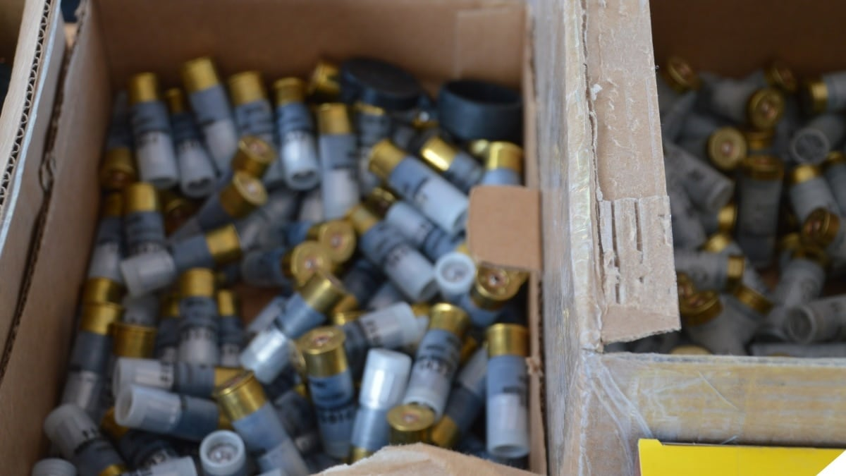 A box of shotgun shells open at the top on a shooting range