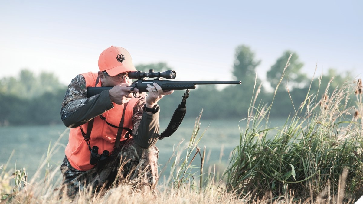 A man in hunter's orange aims a Ruger rifle