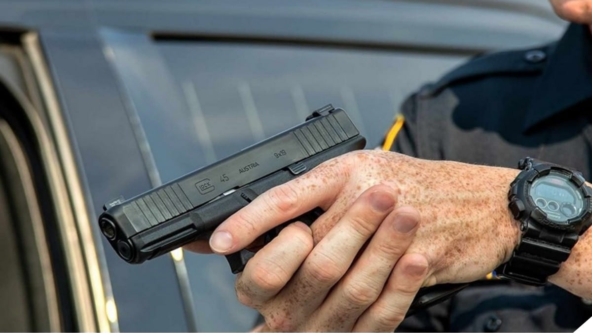 A man in a police officer's uniform holds a Glock G45 pistol