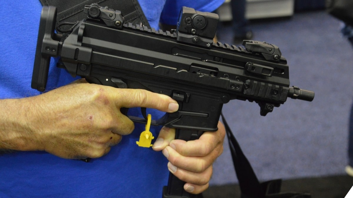 A man in a blue shirt holds a B&T APC9K smg in its compact form