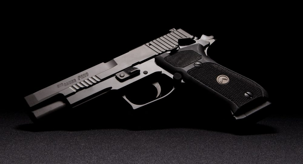 Sig Sauer P220 10mm SAO pistol on a grey background