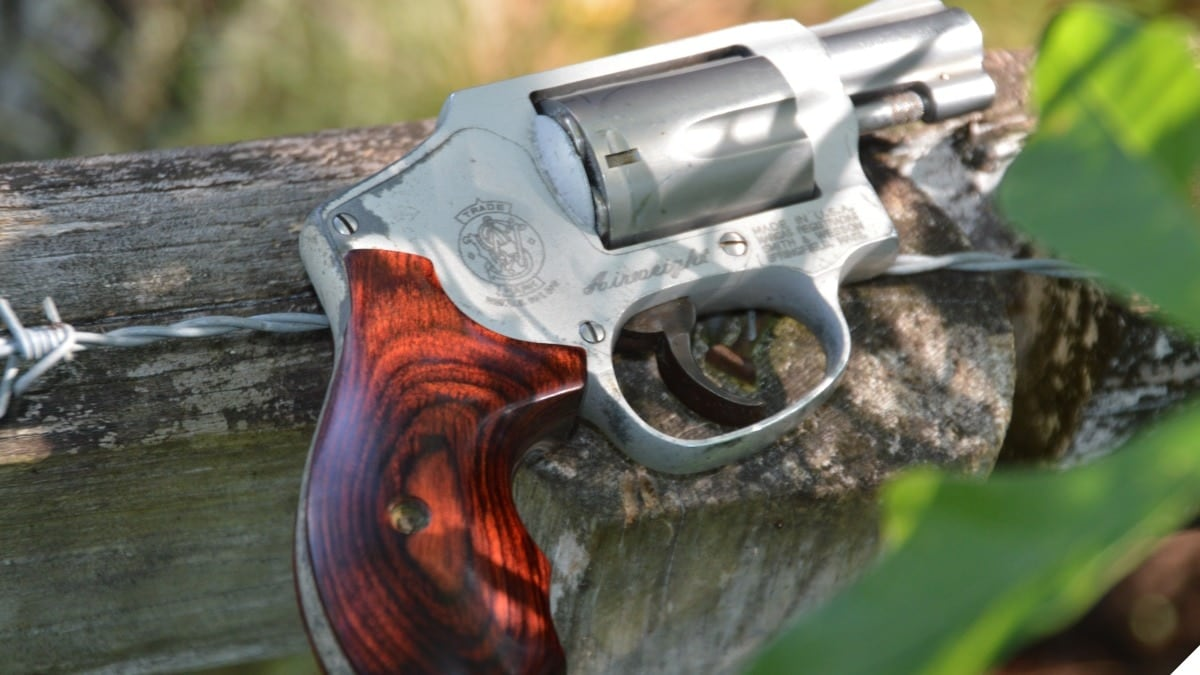 A S&W 642 J-frame snub nosed revolver on a fence with barbed wire