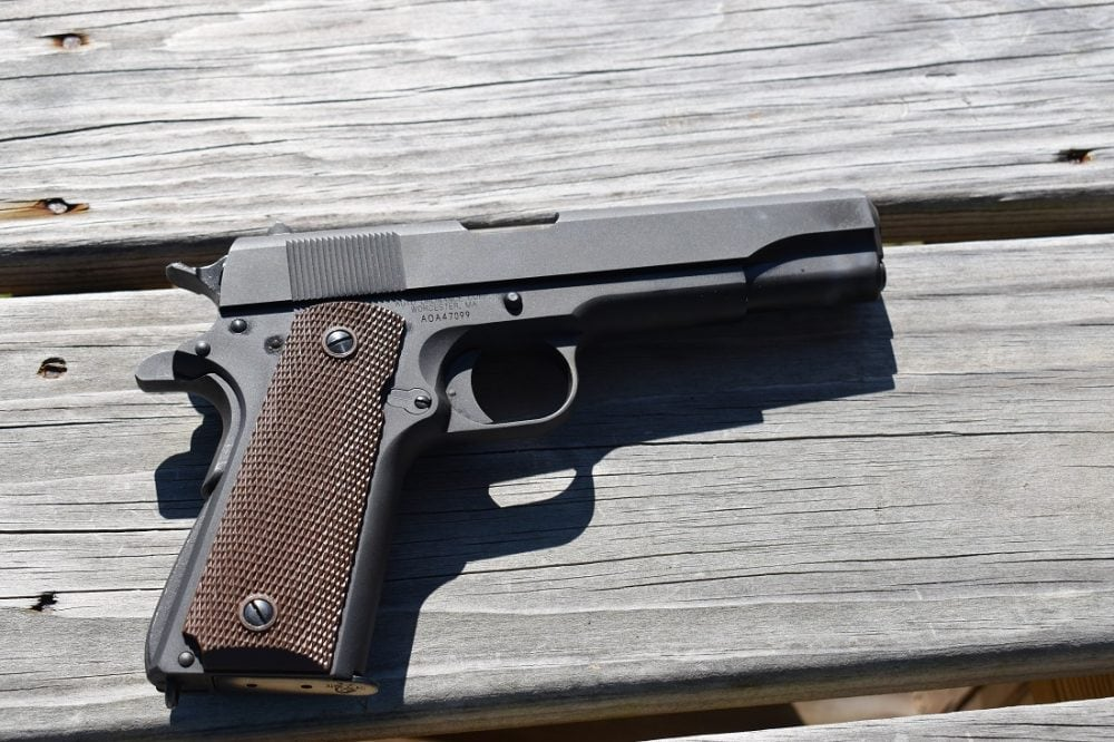 An Auto-Ordnance M1911 on a wooden tabletop in bright sunlight