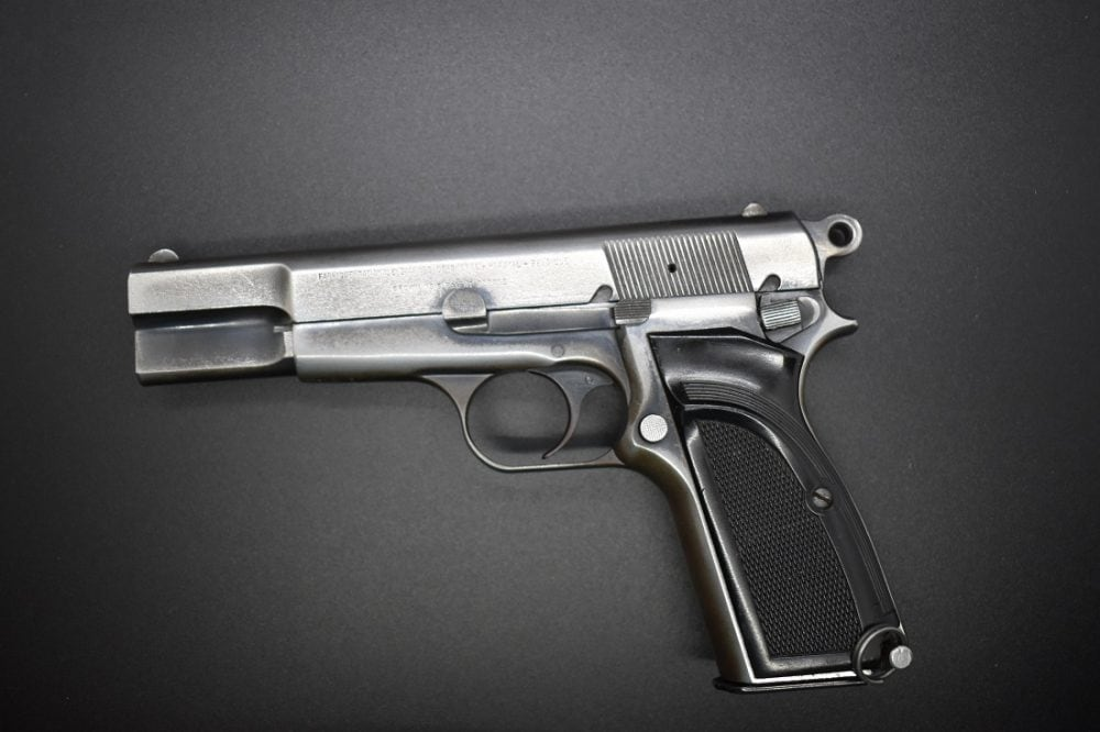 A Browning Hi-Power pistol with a distressed finish