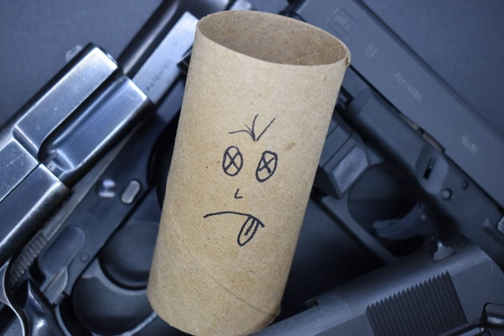 An empty TP tissue roll with a face drawn on it amongst a pile of handguns
