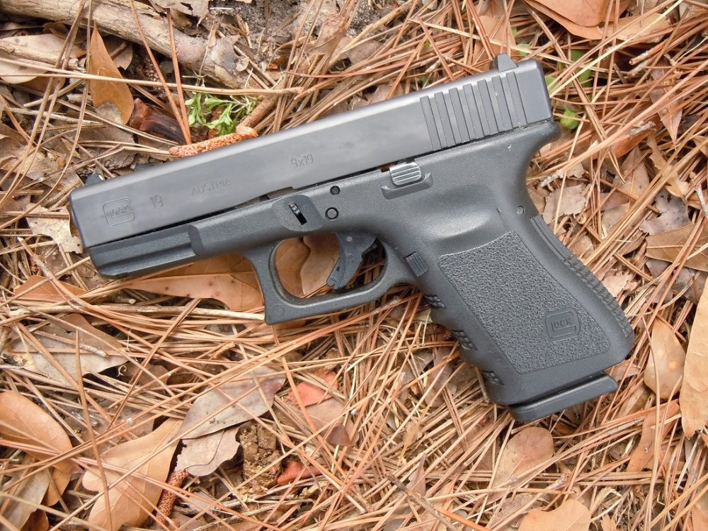 A Gen 3 Glock 19 pistol on a straw-covered ground