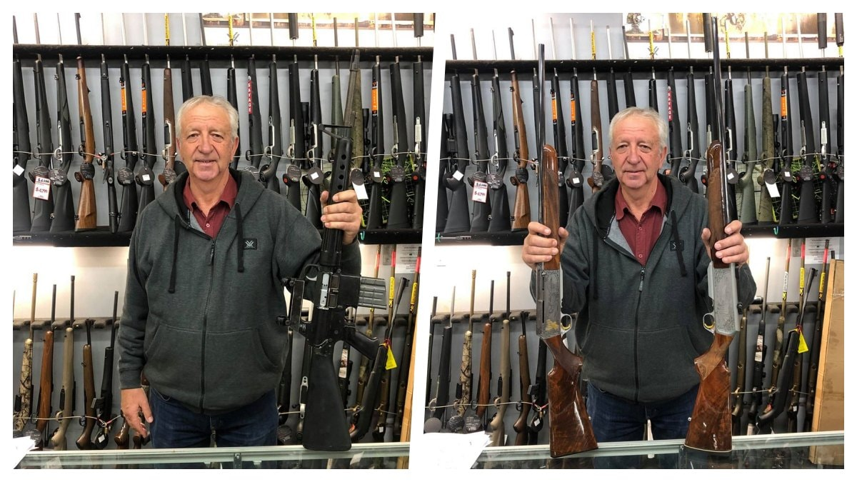A man holds semi-auto rifles behind a gun store counter in New Zealand
