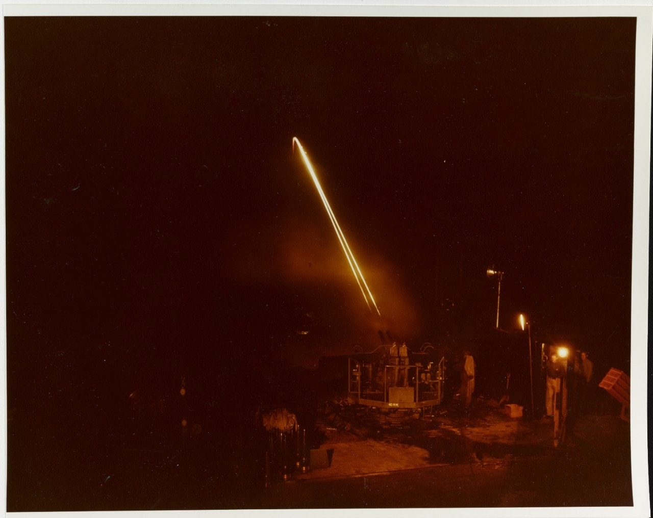 80-G-K-13598 Dahlgren Tracer bullets from a twin 40mm machine gun mount arc across the sky, aimed at targets in the Potomac River,