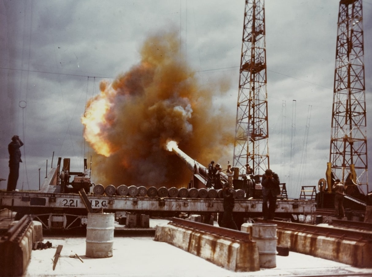80-G-K-13602 Dahlgren 14 - inch gun fires a test round down range, during World War II. Gun crewmen are covering their ears with their hands for noise and shock protection.