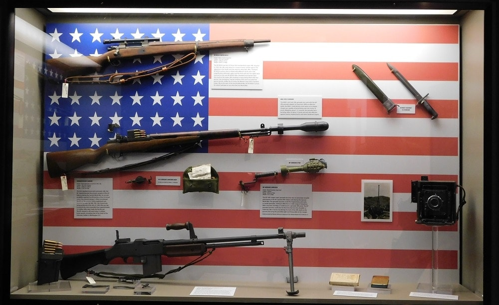 "U.S. military firearms of WWII, including the M3 Grease Gun and Thompson M1 submachine guns, the M1 Carbine, the ""Liberator"" single-shot .45ACP pistol, and M1911A1 .45 Government Issue, (Photo: Chris Eger/Guns.com)"
