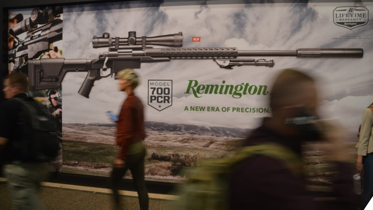People walk in front of a Remington sign at a firearms trade show