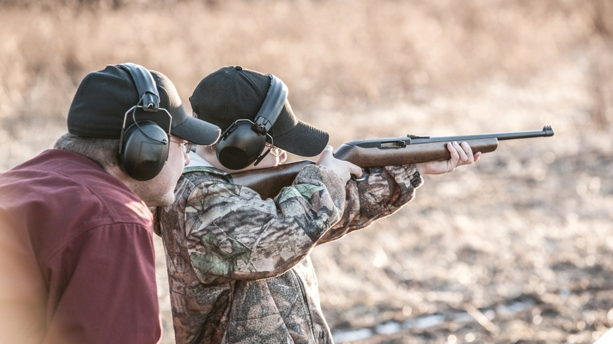 A youth takes aim with a Ruger 10/22 rifle under adult instruction on a shooting range outdoors