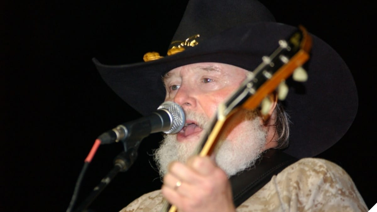 """""""Country music legend Charlie Daniels belts out the tunes at a concert in front of 4th Infantry Division headquarters. Camp Liberty was the final stop on the band's second concert sweep through Iraq as part of the 2006 Stars for Stripes tour."""" (Photo & Caption: U.S. Army)"""