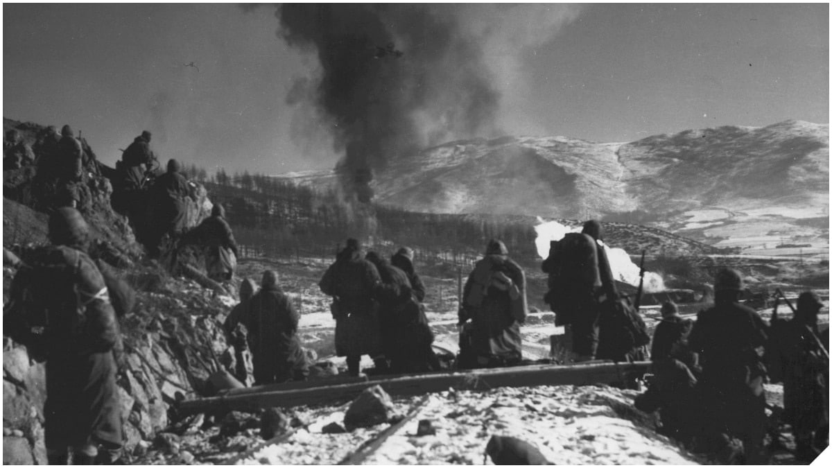 "Marines South of Hagaru-ri, Korea, December 6, 1950 while ""Marine and naval air are working over enemy positions with napalm."" (Photo: USMC Archives)"