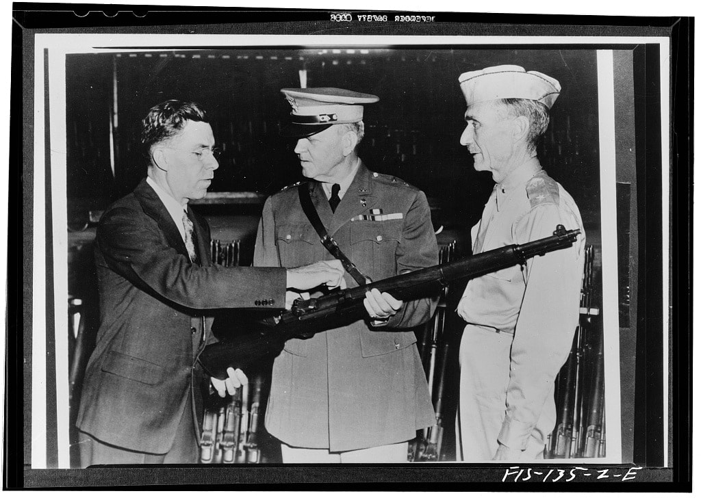Springfield, Massachusetts. John C. Garand, inventor of the Garand rifle, pointing out some of the features of the rifle to Major General Charles M. Wesson
